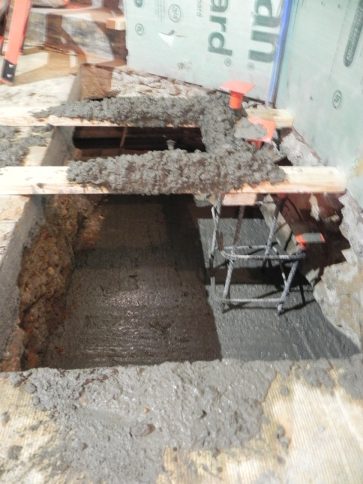The first pour of concrete in the new footing. It extends beneath the 1890 foundation.