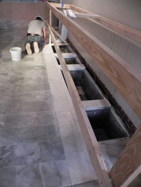 Along the rear of the nave the original tile has been reinstalled where the aisle used to be and the new tile marks the area where pews have been removed. The holes are where return grills will be located