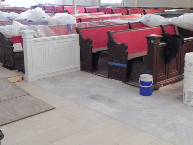New panel (to be painted) and tile at front of the nave where the font will be installed