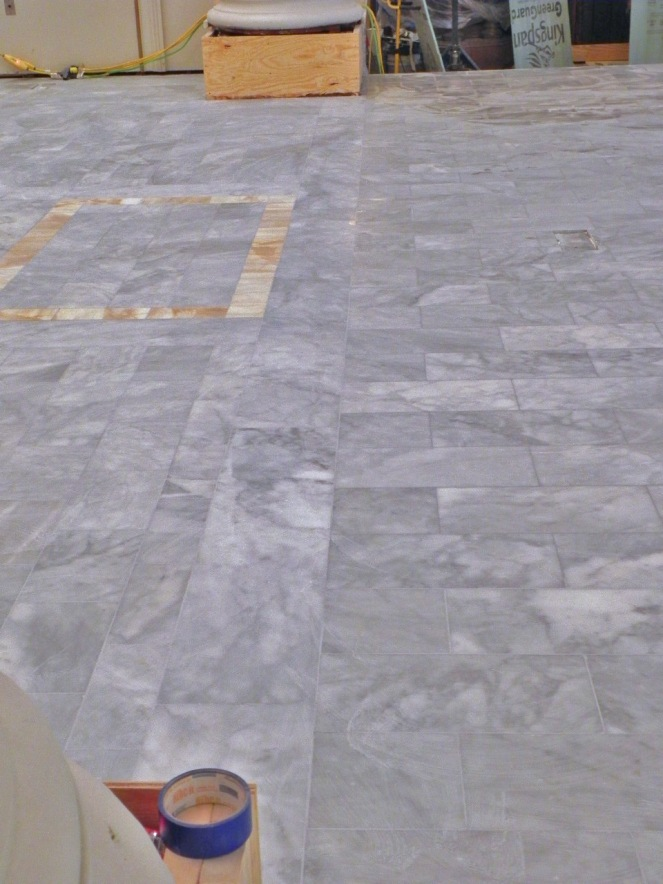 The line of the old chancel is marked with a border and a change in direction and size of the marble tile. When dry the tiles will be much lighter and a uniform color.